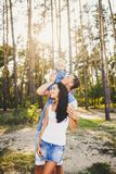 Family mom, dad and daughter sits at the daddy on the shoulders, and parents kiss on the nature in the forest in the summer at sun Royalty Free Stock Image
