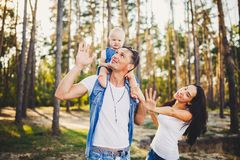 Family mom, dad and daughter sits at the daddy on the shoulders, and parents kiss on the nature in the forest in the summer at sun Royalty Free Stock Photo