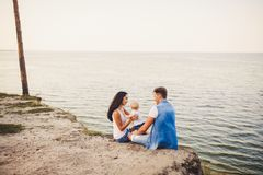 Theme family vacation with small child on the nature and sea. Mom, Dad and daughter of one year are sitting in embrace, girls in t. He hands of man, with his stock image