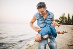 Theme Fatherhood and rest with a child at sea. Young handsome Caucasian father plays plays enjoys throwing up in arms his child up stock photo