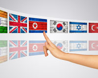 Theme flags various. Finger presses one of virtual screens. Mirror reflection Royalty Free Stock Photos