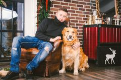 The theme is the friendship of man and animal. Caucasian young male and pet dog breed Labrador Golden Retriever at home inside in stock images