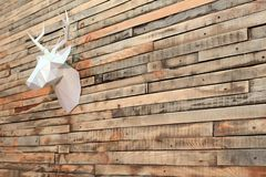 Theme happy new year. Paper deer head hanging on the wall of wooden planks. Perspective at an angle. Copy space. stock photography