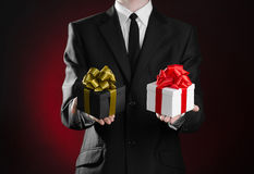 Theme holidays and gifts: a man in a black suit holding two exclusive gift packaged in a black box with gold ribbon and bow and a Royalty Free Stock Photo