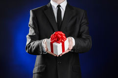 Theme holidays and gifts: a man in a black suit holds an exclusive gift in a white box wrapped with red ribbon and bow on a dark b Stock Photo