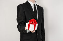 Theme holidays and gifts: a man in a black suit holds an exclusive gift in a white box wrapped with red ribbon and bow isolated on Royalty Free Stock Images
