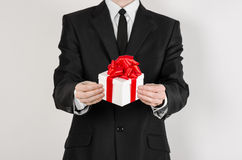 Theme holidays and gifts: a man in a black suit holds an exclusive gift in a white box wrapped with red ribbon and bow isolated on Royalty Free Stock Photos