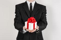 Theme holidays and gifts: a man in a black suit holds an exclusive gift in a white box wrapped with red ribbon and bow isolated on Stock Photos