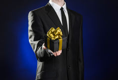 Theme holidays and gifts: a man in a black suit holds exclusive gift wrapped in a black box with gold ribbon and bow on a dark blu Stock Photo