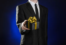 Theme holidays and gifts: a man in a black suit holds exclusive gift wrapped in a black box with gold ribbon and bow on a dark blu Stock Image