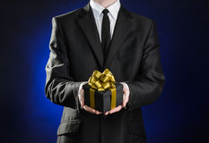 Theme holidays and gifts: a man in a black suit holds exclusive gift wrapped in a black box with gold ribbon and bow on a dark blu Stock Images