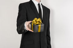 Theme holidays and gifts: a man in a black suit holds exclusive gift wrapped in a black box with gold ribbon and bow isolated on a Royalty Free Stock Image
