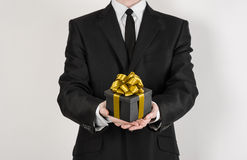 Theme holidays and gifts: a man in a black suit holds exclusive gift wrapped in a black box with gold ribbon and bow isolated on a Stock Image