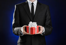 Theme holidays and gifts: a man in a black suit holds exclusive gift wrapped in red box with white ribbon and bow on a dark blue b Royalty Free Stock Photos