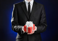 Theme holidays and gifts: a man in a black suit holds exclusive gift wrapped in red box with white ribbon and bow on a dark blue b Stock Image