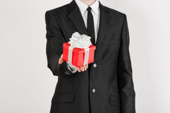 Theme holidays and gifts: a man in a black suit holds exclusive gift wrapped in red box with white ribbon and bow isolated on a wh Stock Photos