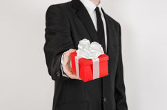 Theme holidays and gifts: a man in a black suit holds exclusive gift wrapped in red box with white ribbon and bow isolated on a wh Royalty Free Stock Photos