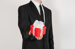 Theme holidays and gifts: a man in a black suit holds exclusive gift wrapped in red box with white ribbon and bow isolated on a wh Stock Photo