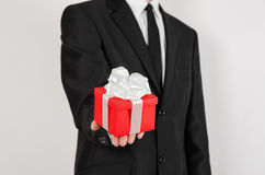 Theme holidays and gifts: a man in a black suit holds exclusive gift wrapped in red box with white ribbon and bow isolated on a wh Royalty Free Stock Image