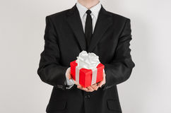Theme holidays and gifts: a man in a black suit holds exclusive gift wrapped in red box with white ribbon and bow isolated on a wh Stock Photography