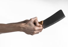 The theme of the kitchen: Chef hand holding a large kitchen knife for cutting meat on a white background isolated Royalty Free Stock Photos