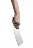 The theme of the kitchen: Chef hand holding a large kitchen knife for cutting meat on a white background isolated Royalty Free Stock Images