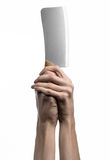 The theme of the kitchen: Chef hand holding a large kitchen knife for cutting meat on a white background isolated Stock Image