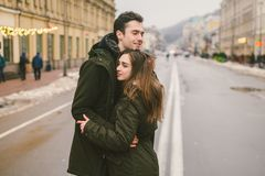 Theme love and romance. Caucasian young people heterosexual couple in love students boyfriend girl hugging and kissing on center. Of road in center of European royalty free stock images