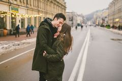 Theme love and romance. Caucasian young people heterosexual couple in love students boyfriend girl hugging and kissing on center. Of road in center of European stock photo