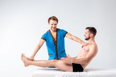 Theme massage and body care. Beautiful caucasian man in blue uniform and beard diagnosing abdominal muscles, stretching guy with g royalty free stock photos
