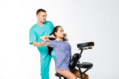 Theme massage and office. young male therapist in blue suit doing back massage with his knee braced in the spine of female worker, Royalty Free Stock Photo