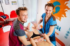 Theme medicine and rehabilitation. two twin brothers Young male doctor masseur treats massaging a young woman on a massage table stock image