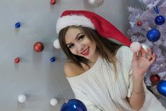 Portrait of a long-haired blonde in a red Santa Claus hat and knitted sweater with a bare shoulder. Christmas tree and colored bal stock photography