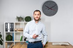 Theme office business. Handsome young caucasian man confident and strong with beard standing in bright room on working place. dres stock images