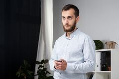 Theme office business. Handsome young caucasian man confident and strong with beard standing in bright room on working place. royalty free stock photos