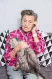 Theme old person uses technology. Mature contented joy smile active gray hair Caucasian wrinkles woman sitting home royalty free stock image