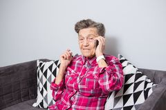 Theme old person uses technology. Mature happy joy smile active gray hair Caucasian wrinkles woman sitting home in. Living room on the sofa and using a mobile stock image