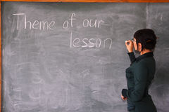 Theme of our lesson. Woman writes on a blackboard Royalty Free Stock Images