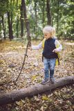 Theme outdoor activities in nature. Funny little Caucasian blonde girl walks walks hiking in the forest on rough terrain with a royalty free stock photos