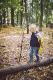 Theme outdoor activities in nature. Funny little Caucasian blonde girl walks walks hiking in the forest on rough terrain with a royalty free stock image