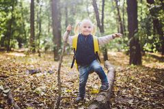 Theme outdoor activities in nature. Funny little Caucasian blonde girl walks walks hiking in the forest on rough terrain with a stock photos