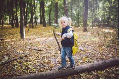 Theme outdoor activities in nature. Funny little Caucasian blonde girl walks walks hiking in the forest on rough terrain with a stock image