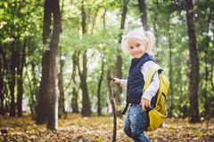 Theme outdoor activities in nature. Funny little Caucasian blonde girl walks walks hiking in the forest on rough terrain with a stock photography
