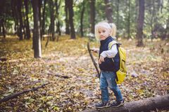 Theme outdoor activities in nature. Funny little Caucasian blonde girl walks walks hiking in the forest on rough terrain with a royalty free stock photo