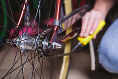 Theme repair bikes. Close-up of a Caucasian man`s hand use a Chain Lubricant in a yellow lubricator for llubricator a bicycle cha stock photo