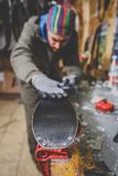 Theme repairs and maintenance of skis. The male worker is repairing work clothes, applying wax on the sliding surface onto skis mo stock image