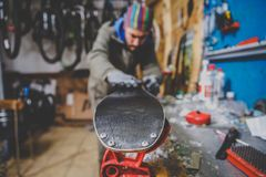 Theme repairs and maintenance of skis. The male worker is repairing work clothes, applying wax on the sliding surface onto skis mo royalty free stock photography