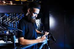 Theme sale and repair of bicycles. Young and stylish with a beard and long hair, a Caucasian man uses a tool to set up and repair Stock Images