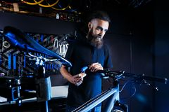 Theme sale and repair of bicycles. Young and stylish with a beard and long hair, a Caucasian man uses a tool to set up and repair Royalty Free Stock Photo