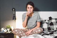 The theme is seasonal cold, runny nose flu virus infection. Young caucasian woman at home bedroom bed uses spray drops of medicine royalty free stock photo